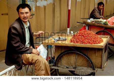 Kunming China - April 24 2006: Street vendors selling fresh cherries and watermelon from small wheeled carts on Renmin Road