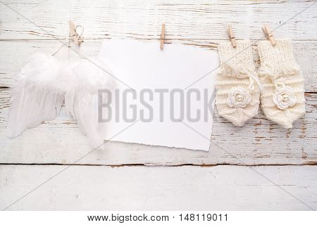 Baby New Born or baptism Greeting Card. Blank card with baby girl gloves and angel wings on white wooden background.