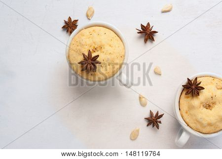 Pumpkin mug-cakes on a white wooden table, surrounded by spices and pumpkin seeds, top view, copy space