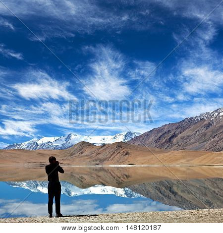 LADAKH, INDIA - JUNE 20, 2012: Tourist with camera walking on Thatsang Karu lake in Ladakh, Jammu and Kashmir State of India