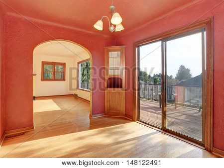 Hallway Interior In Red Tones With Hardwood Floor. The Room Has Exit To Balcony.