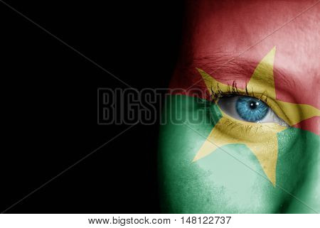 A young female with the flag of Burkina Faso painted on her face on her way to a sporting event to show her support.