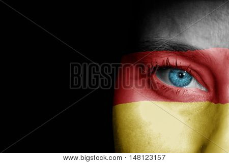 A young female with the flag of Germany painted on her face on her way to a sporting event to show her support.