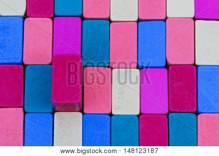 Texture of multicolored wooden blocks placed one near the other end face with one protruding block