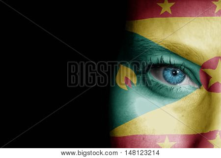 A young female with the flag of Grenada painted on her face on her way to a sporting event to show her support.