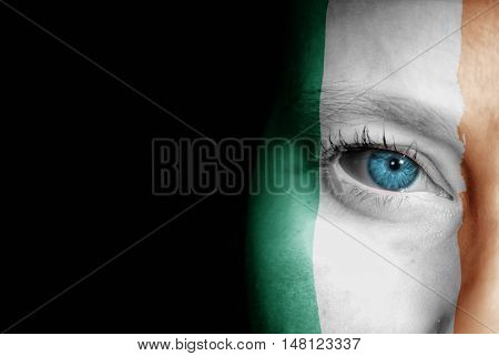 A young female with the flag of Ireland painted on her face on her way to a sporting event to show her support.