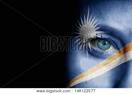 A young female with the flag of Marshall Islands painted on her face on her way to a sporting event to show her support.