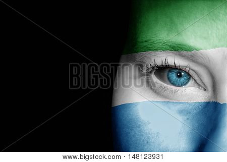 A young female with the flag of Sierra Leone painted on her face on her way to a sporting event to show her support.