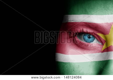 A young female with the flag of Suriname painted on her face on her way to a sporting event to show her support.