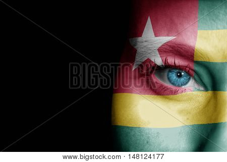 A young female with the flag of Togo painted on her face on her way to a sporting event to show her support.