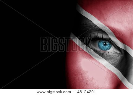 A young female with the flag of Trinidad and Tobago painted on her face on her way to a sporting event to show her support.