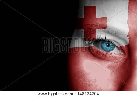 A young female with the flag of Tonga painted on her face on her way to a sporting event to show her support.