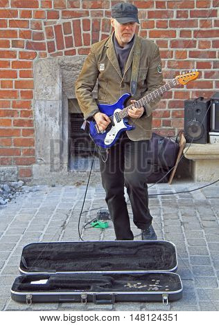 Krakow, Poland - October 29, 2015: street musician is playing guitar outdoor in Krakow, Poland