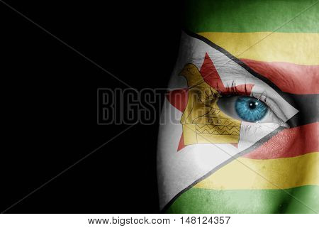 A young female with the flag of Zimbabwe painted on her face on her way to a sporting event to show her support.