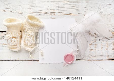 Baby New Born or baptism Greeting Card. Blank card with baby girl shoes and angel wings on white wooden background.