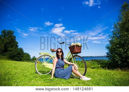 Happy Woman Sitting On The Grass With Vintage Bicycle On The Sea Coast Over Blue Sky Background