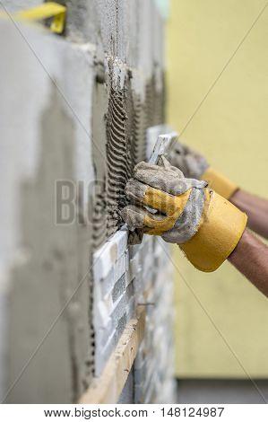 Gloved hands of worker installing ceramic wall tiles over freshly scored mortar compound.