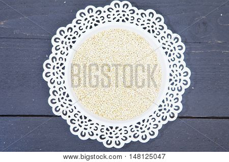 White quinoa on white plate on black wooden background