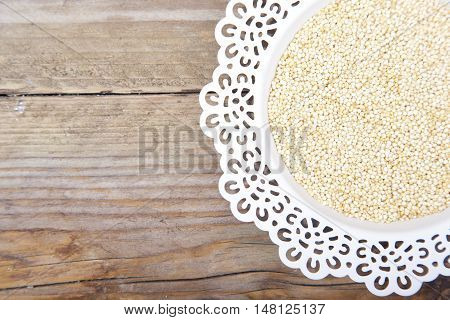 White quinoa on white plate on brown wooden background