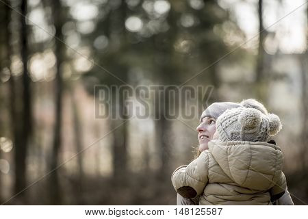 Young mother carrying her young child outdoors in the countryside in winter dressed in warm woolly hats with copy space.
