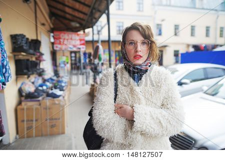Beautiful young woman in a white jacket and scarf walking down the street with a bag on a background of stalls and cars.