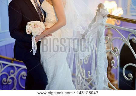 Wedding Couple With Bouquet. Female And Male Portrait. Beautiful Model Girl In White Dress. Man In S