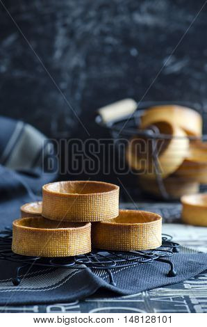 Stack of empty tartlets on dark background