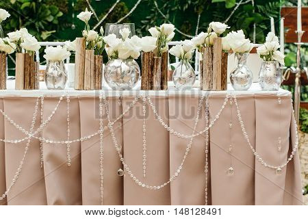 Beautiful decor at the wedding. Flowers standing on the table, adorned with glass garlands