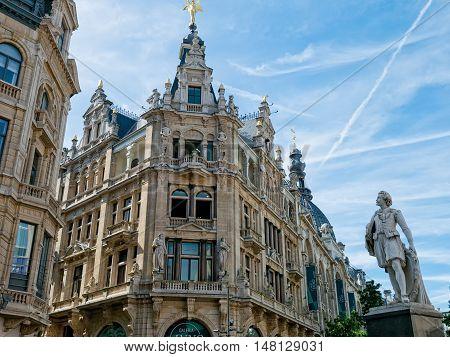 Statue of Flemish painter Anthony Antoon van Dijck and landmark buildings along Meir street in Antwerp, Belgium