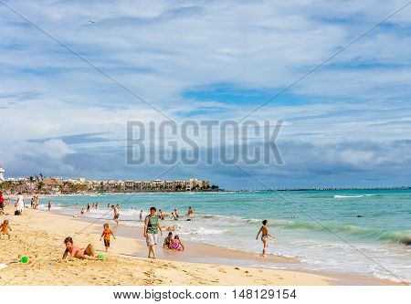 Cancun Mexico - December 12 2006 : Beach scene with children playing and adults on the beach Cancun Mexico