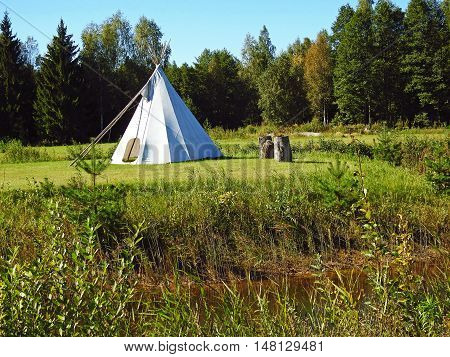 White wigwam on green field on forest background.