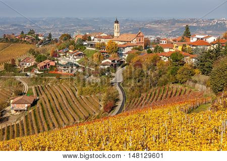 Small italian town among yellow vineyards on the hills in autumn in Piedmont, Northern Italy.