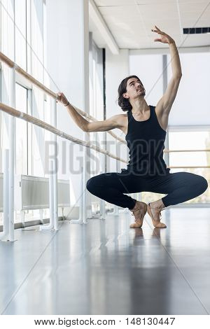 Young Male Ballet Dancer Posing Near Barre, Man Practicing In Dance Studio