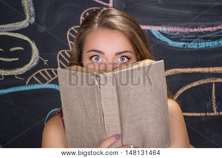 Perplexed young student girl in red dress and red glasses reading a book hides behind it