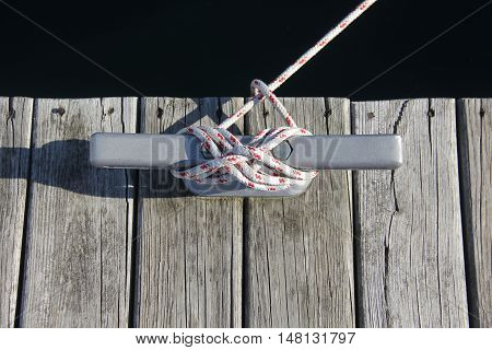 A rope is tied to a cleat on a dock