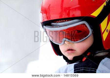 Retrato de niño pequeño con casco en vacaciones de invierno