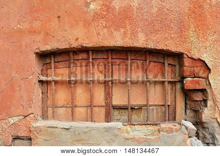 Old terracotta plastered wall of red brick with closed window. Grunge texture background