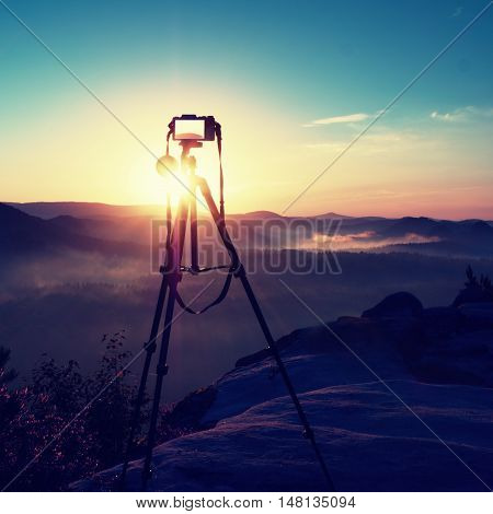 Tripod with running camera on peak ready for photography. Sharp autumn rocky peaks increased from gold fog. Vivid and strong vignetting effect.
