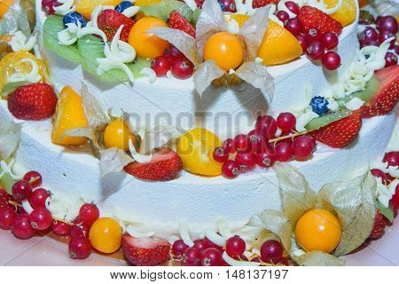 three-tiered white cake with fruits and berries