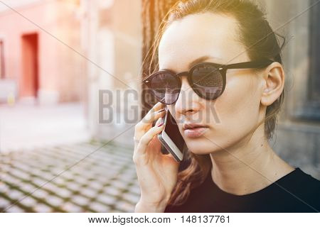 Close up portrait of young Caucasian woman in hipster sunglasses speaking on the phone. Beautiful female is talking on smart phoneon the street. Having mobile phone conversation. Copy space for your advertisement