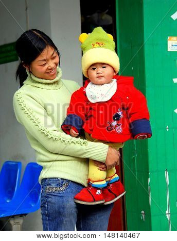 Li'an Village China - November 26 2007: Mother holding her baby all bundled up in a red jacket and knit cap