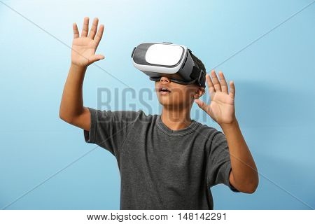African-American boy wearing virtual reality glasses on blue background