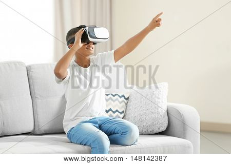 African-American boy wearing virtual reality glasses and sitting on sofa in a room