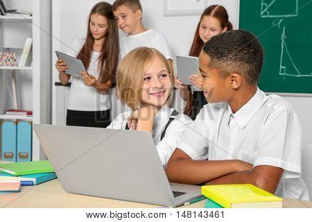 Schoolchildren sitting in classroom with laptop