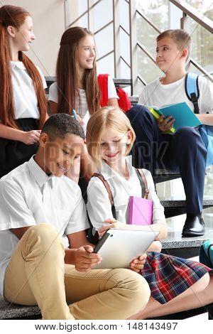 Schoolchildren sitting on stair-steps near window at school