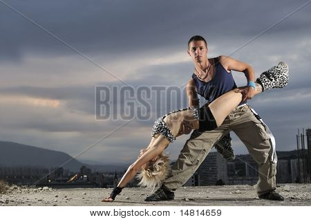romantic urban couple dancing on top of the bulding at night scene
