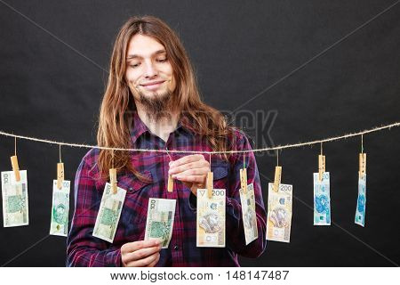 Riches and fortune. Young happy man with a lot of money on black background. Winning the lottery concept.