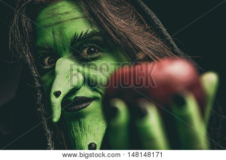 Evil Witch Looking At Camera Holding A Red Apple