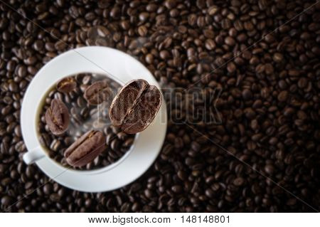 White cup coffee beans with falling beans from top with beans coffee textured background.