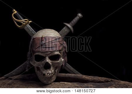 pirate skull with two swords over darkness background still life style